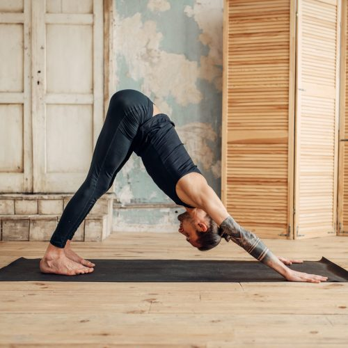 Male yoga with tattoo on hand doing stretching exercise on mat in gym with grunge interior. Fit workout indoors